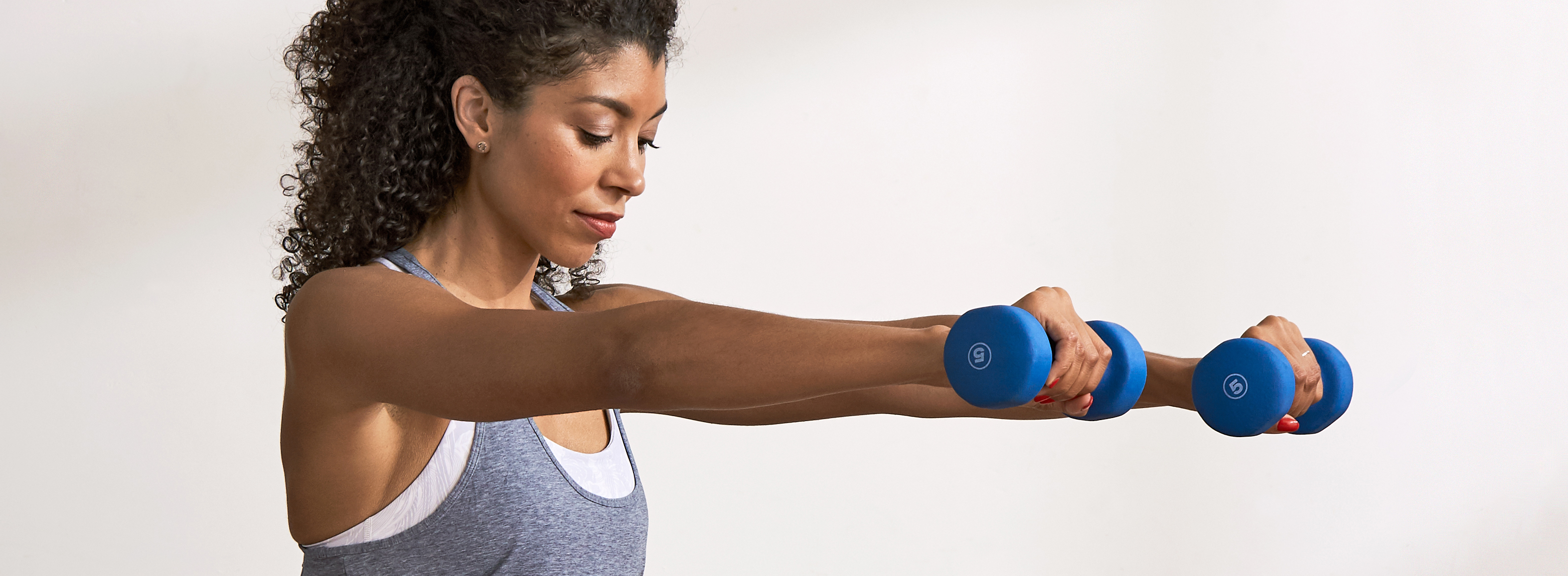 woman holding blue free weights